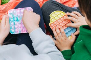Close up on children Siblings playing with colorful poppit sensory game. Teen kids hands Pushing